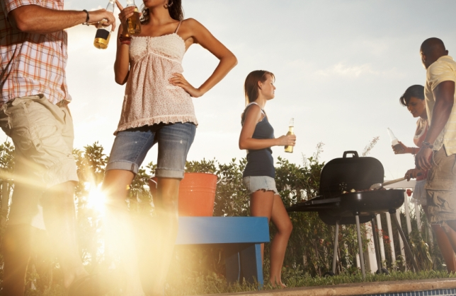 Group of multiracial friends with barbecue and beer bottle enjoying their vacation